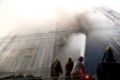 Miembros del cuerpo de bomberos de Bangladesh intenta apagar el incendio