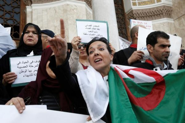 Judicial officers carry banners and national flags during a protest calling on President Abdelaziz Bouteflika to quit