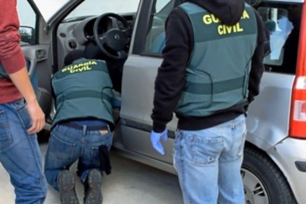 Guardias civiles registran el coche del detenido.