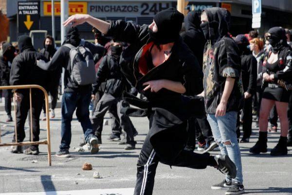 Un grupo de encapuchados han lanzado piedras y otros objetos contra el cordón de seguridad que han montado los Mossos d'Esquadra en la plaza España de Barcelona, donde se celebrará un acto de Vox.