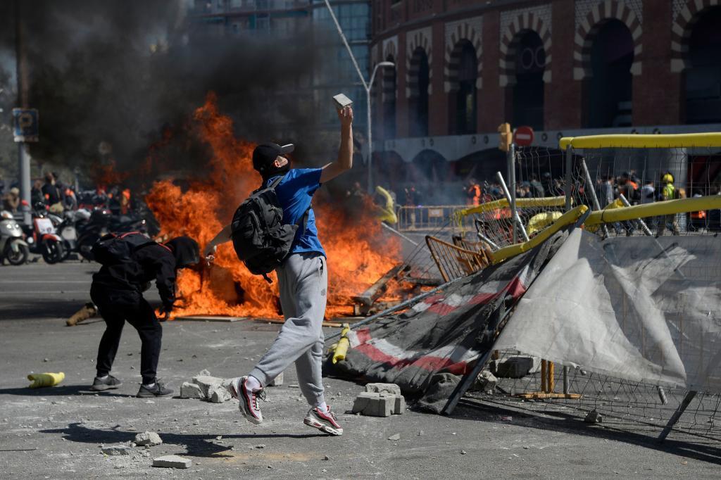 Radicales lanzan adoquines a los Mossos tras una barricada en llamas.