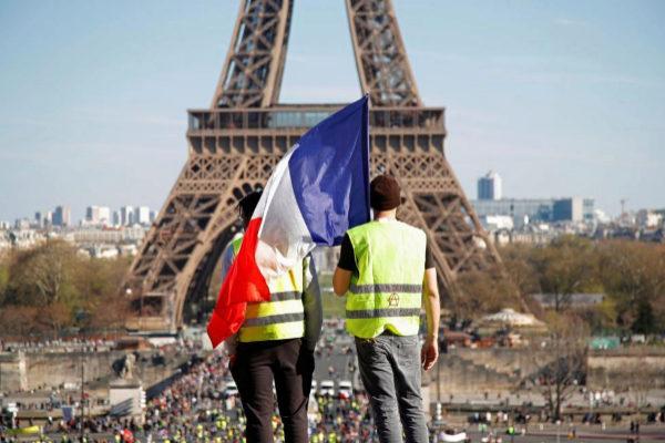 Dos manifestantes con chalecos amarillos y la bandera francesa, frente a la Torre Eiffel.