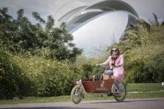 La responsable de  ValenciaNannies.es, Sigrid van der Spoel, en su bicicleta con el anagrama de su empresa en el cauce del río.