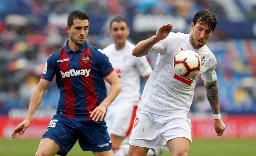 El jugador del Eibar Sergi Enrich controla el balón ante el jugador del Levante UD Sergio Postigo.