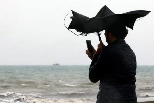 Una persona hace una fotografía en la Playa de la Malvarrosa de Valencia bajo la lluvia y el fuerte viento, este domingo