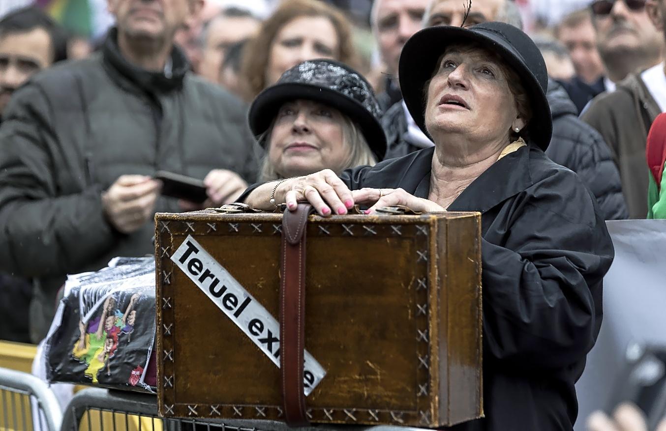 Una mujer con una maleta y la pegatina de Teruel existe, en la...