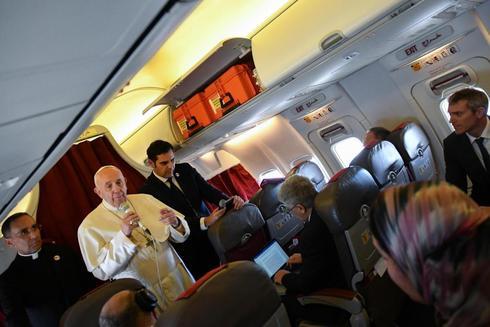 El Papa Francisco habla con los periodistas que le acompañan en el avión papal.