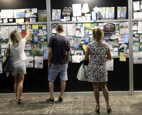 Varios jóvenes consultan un tablón de anuncios en una feria de empleo celebrada en Barcelona.