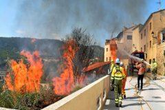 Bomberos participan en tareas de extinción de un fuego próximo a viviendas.