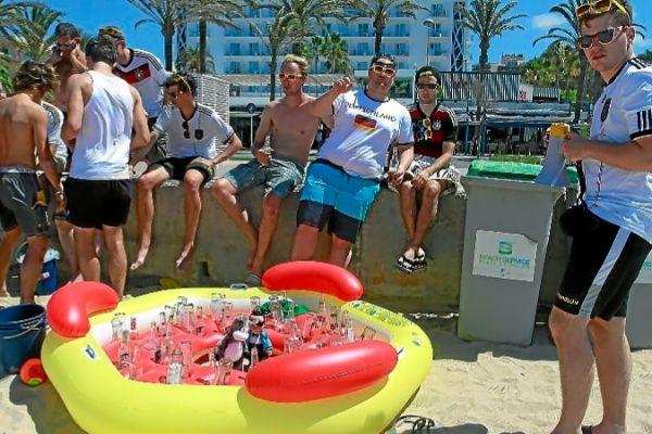Turistas en Playa de Palma consumiendo alcohol en primera línea.