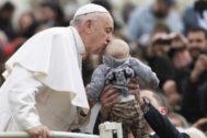 El <HIT>papa</HIT> Francisco saluda a un bebé en la plaza de San Pedro del Vaticano.