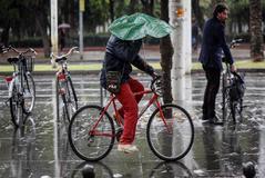 Una persona circula en bicicleta mientras intenta resguardarse de la lluvia con un paraguas, en el centro de Sevilla.