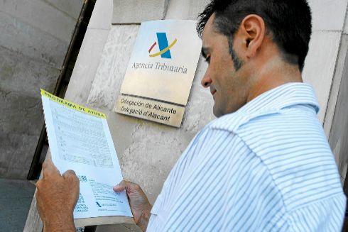 Un hombre con los documentos de sus impuestos en la sede de la Agencia Tributaria de Alicante.