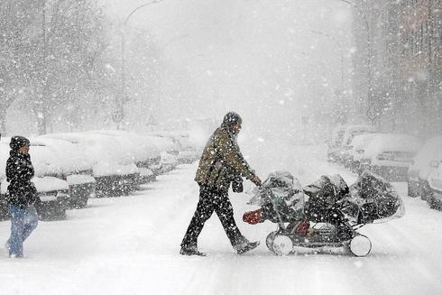 Un padre empula una silleta de trillizos durante una nevada en Vitoria.