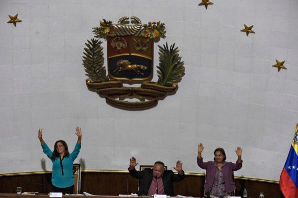 El presidente de la Asamblea Constituyente venezolana, Diosdado Cabello, levanta las manos junto a a Gladya Requena (d) y la vice presidenta Tania Díaz.