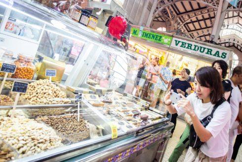 Una turista japonesa hace una foto a unos frutos secos en el Mercado Central de Valencia, en una imagen de archivo.