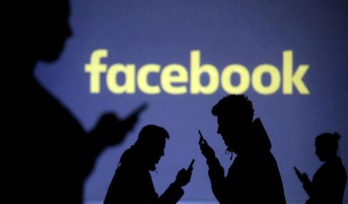 Las siluetas de personas viendo sus móviles junto al logotipo de Facebook