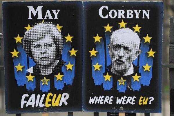 Dos carteles con la imagen Theresa May y Jeremy Corbyn.