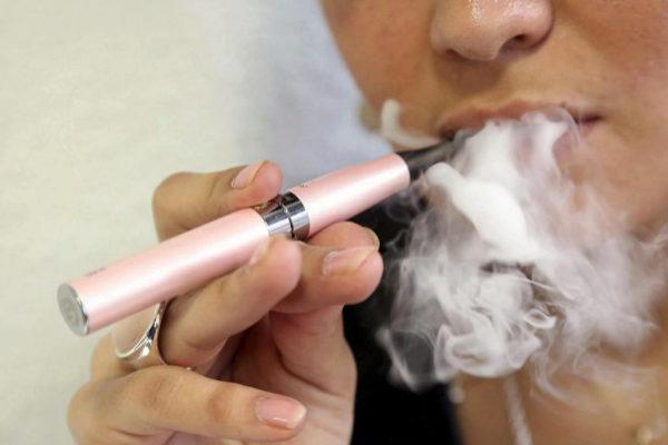 Una mujer fumando un cigarrillo electrónico.