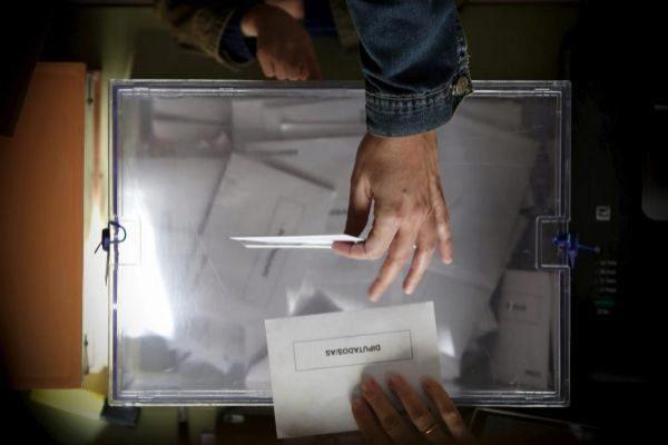 Una persona votando en un colegio electoral.