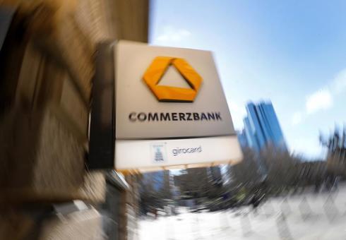 Cartel que anuncia un cajero de Commerzbank en Francfort con la sede del banco al fondo.