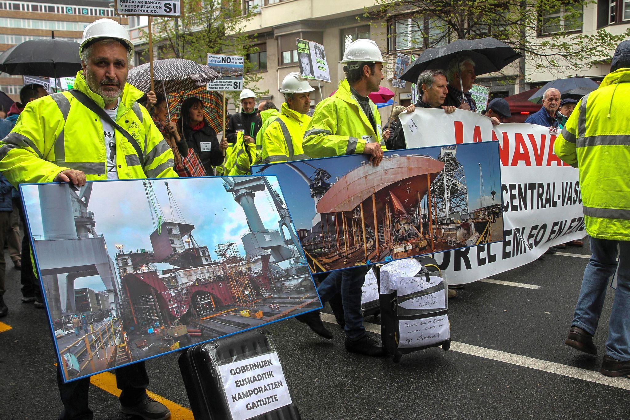 Trabajadores de La Naval con sus maletas e imágenes de su astillero durante la manifestación en Bilbao.