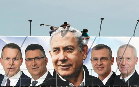 FILE PHOTO: Labourers work on hanging up a Likud election campaign banner depicting Israeli Prime Minister Benjamin <HIT>Netanyahu</HIT> with his party candidates, in Jerusalem