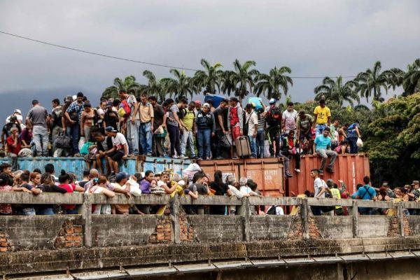 Venezolanos subidos a un contenedor intentan cruzar el puente Simón Bolívar.