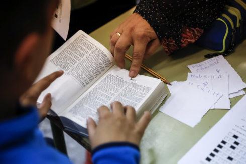 Un chico estudia en un colegio con ayuda de sus profesora.