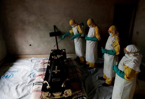 FILE PHOTO: Healthcare worker sprays room during funeral of suspected...