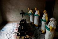 FILE PHOTO: Healthcare worker sprays room during funeral of suspected <HIT>Ebola</HIT> victim