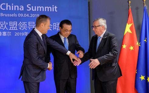 El primer ministro chino, Li Keqiang (c), saluda al presidente del Consejo Europeo, Donald Tusk (i), y al presidente de la Comisión Europea, Jean-Claude Juncker (d), este martes en la sede del Consejo Europeo en Bruselas (Bélgica).