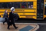 Dos niños caminando al lado de un autobús escolar en Brooklyn, Nueva York.