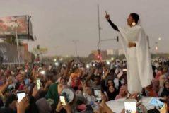 Imagen de la mujer, subida sobre un coche, cantando y arengando a los manifestantes.