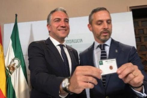 El consejero de Presidencia, Elías Bendodo, y el de Hacienda, Juan Bravo, muestran la tarjeta de 'céntimo'.