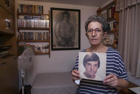 Antonia Guevara, madre de David Guerrero, el niño pintor de Málaga, en su casa sostiene un retrato de su hijo desaparecido hace más de 30 años.