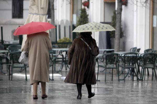 Dos ancianas pasean frente a una terraza vacía en Madrid.