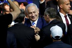 Israeli Prime Minister Benjamin <HIT>Netanyahu</HIT> is greeted by supporters of his Likud party as he arrives to speak following the announcement of exit polls in Israel's parliamentary election at the party headquarters in Tel Aviv, Israel