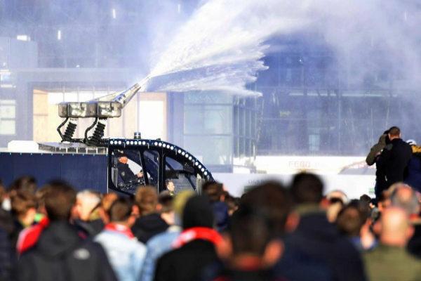 La policía holandesa repele con agua a hinchas antes del partido.
