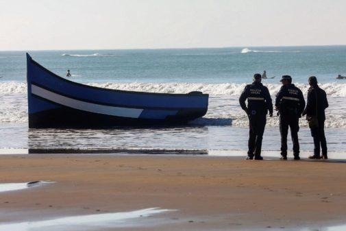 Unos policías observan los restos de una patera llegada a las costas de Cádiz.