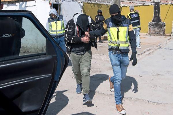 Uno de los seis detenidos siendo conducido al furgón policial.