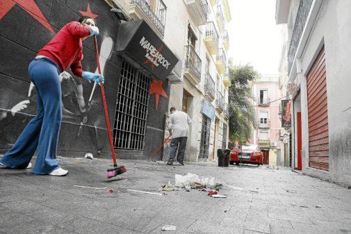 Varios empleados de locales del centro de la ciudad limpiando la calle, en imagen de archivo.