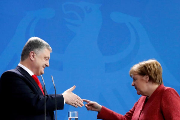 German Chancellor Angela <HIT>Merkel</HIT> and Ukrainian President Petro Poroshenko gesture as they leave after a joint news conference in Berlin