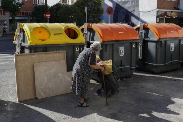 Una mujer lleva sus bolsas de envases al contenedor amarillo en Madrid.