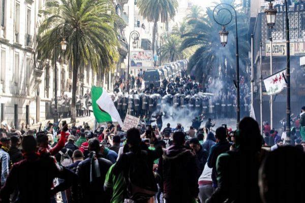 Manifestantes argelinos frente a la policía antidisturbios, durante las protestas de este viernes en Argel.