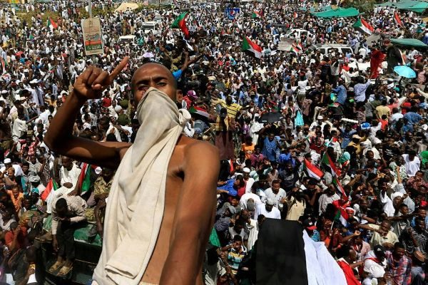 A Sudanese demonstrator gestures while riding atop a military truck as...