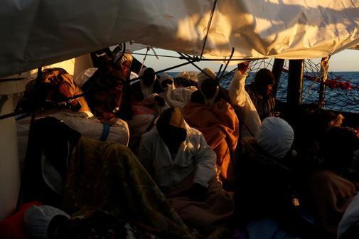 Un grupo de personas a bordo del 'Alan Kurdi' descansa, ya cerca de la costa de Malta.