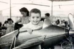 Fotografía en blanco y negro de un niño con una avioneta