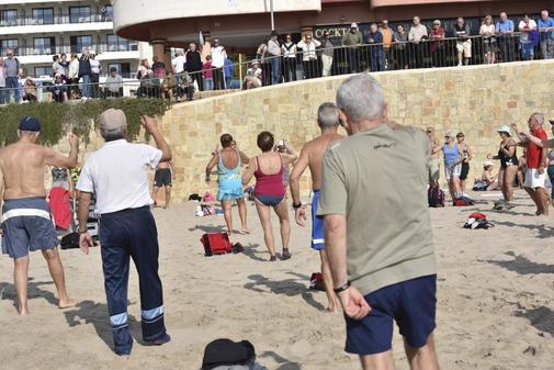 Un grupo de ancianos realiza actividad física en la Playa de Poniente de Benidorm durante unas vacaciones de invierno, en imagen de archivo.