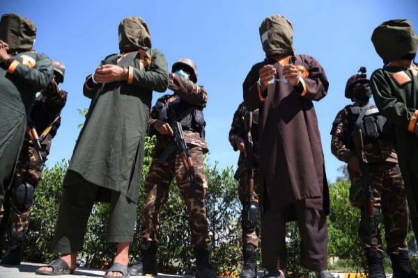 Agentes escoltan a un grupo de sospechosos de pertenecer a los talibán